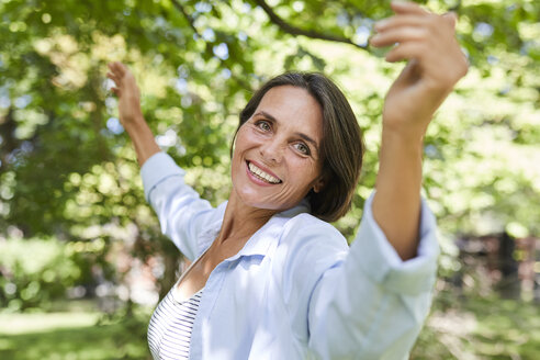 Portrait of smiling mature woman dancing in nature - PNEF00858