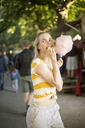 Portrait of young woman eating pink candy floss on streetfood festival - JESF00002
