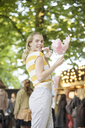 Portrait of young woman with pink candy floss on streetfood festival - JESF00008