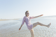 Netherlands, young woman splashing water at the beach in summer - JESF00011