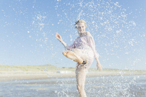 Netherlands, young woman splashing water at the beach in summer - JESF00014