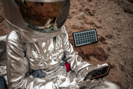Spaceman sitting on nameless planet, charging device with solar panel - VPIF00450