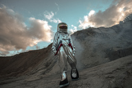 Spaceman exploring nameless planet, walking in a dust cloud - VPIF00477