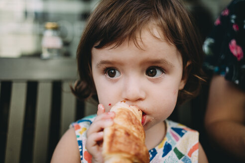 Portrait of baby girl eating a croissant - GEMF02242