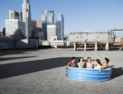 A group of friends, men and women sitting in a small inflatable water pool on a city rooftop, cooling down. - MINF06046