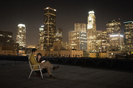 A couple on a rooftop overlooking Los Angeles at night, one seated, looking at a smart phone. - MINF06067