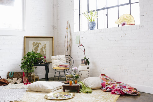 A light airy room with whitewashed walls. Cushions and possessions scattered across the floor. - MINF06091