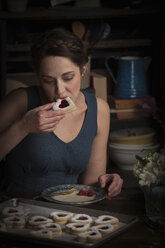 Valentine's Day baking, young woman sitting in a kitchen, eating a heart shaped biscuit. - MINF06172