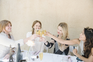 Four smiling women sitting at a table, holding glasses of champagne, toasting. - MINF06277