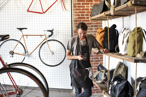 A man working in a bicycle repair shop looking at his smart phone. - MINF06289