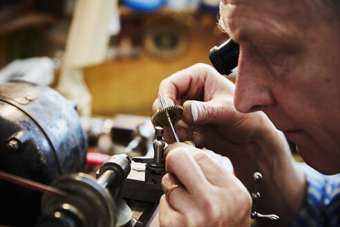 A clock maker and repairer using an eye loupe to work on a cog wheel, clock parts. - MINF06322