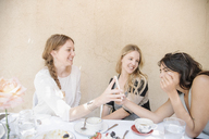 Three smiling young women sitting round a table with food and drink, looking at a cell phone. - MINF06349