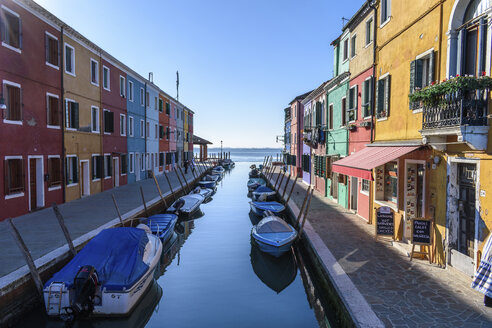Small motorboats moored in narrow canal lines with colourful houses, Venice, Italy. - MINF06493
