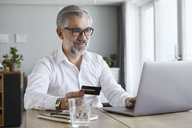 Portrait of content mature man  paying online with credit card at home - RBF06468