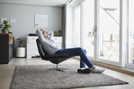 Mature man relaxing on leather chair in his living room - RBF06474