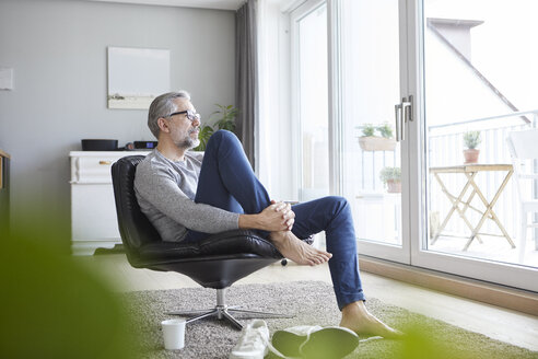 Mature man relaxing on leather chair in his living room looking out of window - RBF06480
