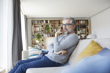 Pensive mature man sitting on couch in his living room looking out of window - RBF06486