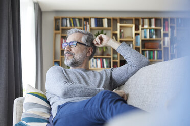 Mature man relaxing on couch at home looking out of window - RBF06489