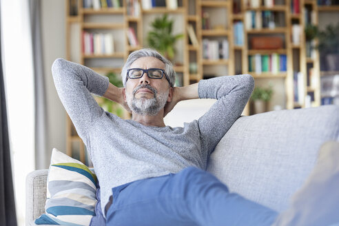 Portrait of mature relaxing on couch at home - RBF06492