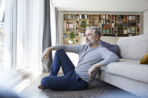 Mature man sitting on floor of his living room looking out of window - RBF06495