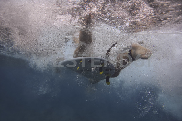 Maledives, Indian Ocean, surfer on surfboard, underwater shot - KNTF01189