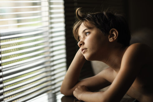 Portrait of daydreaming little girl looking out of window - JSMF00380