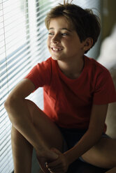 Portrait of smiling little girl looking out of window - JSMF00389