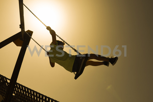 Little girl swinging at backlight - JSMF00404