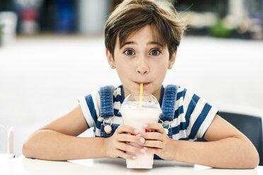 Portrait of little girl drinking strawberry milkshake at pavement cafe - JSMF00410