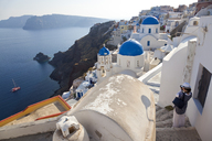 High angle view of traditional white washed church with bright blue dome on the island of Santorini, Greece. - MINF06573