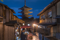 Japanese couple in traditional dress standing in a street at night, a pagoda in the background. - MINF06588