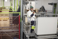 Worker sitting at apple packing machine - ZEF15930