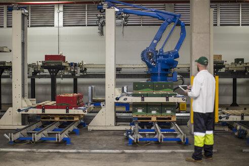 Worker checking machine progress using control panel - ZEF15952
