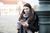 Portrait of smiling young woman with coffee to go and cell phone leaning against lamp pole - JESF00026