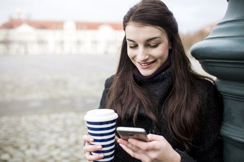 Portrait of young woman with coffee to go leaning against lamp pole looking at cell phone - JESF00029