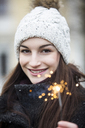 Portrait of smiling young woman with sparkler wearing bobble hat - JESF00032