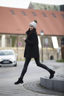 Portrait of smiling young woman with cell phone crossing the street - JESF00035