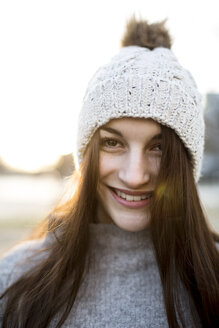 Portrait of smiling young woman wearing bobble hat in winter - JESF00044
