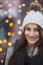 Portrait of smiling young woman wearing bobble hat at Christmas time - JESF00047