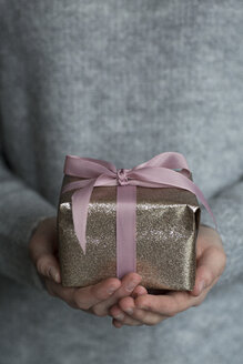 Woman's hand holding present, close-up - JESF00053