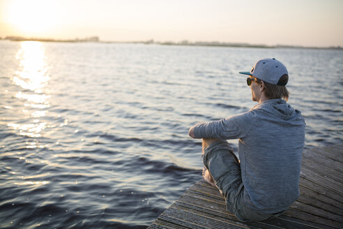 Man sitting on wooden boardwalk, enjoying sunset - JESF00062