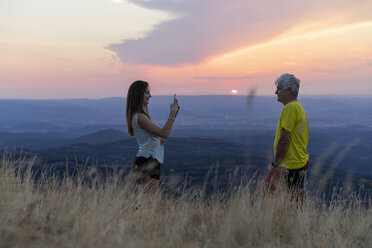 Spain, Catalonia, Montcau, senior father and adult daughter taking a cell phone picture on top of hill during sunset - AFVF01360