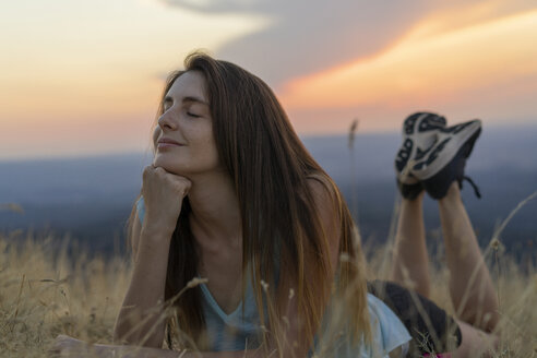 Smiling young woman with closed eyes lying in grass during sunset - AFVF01366