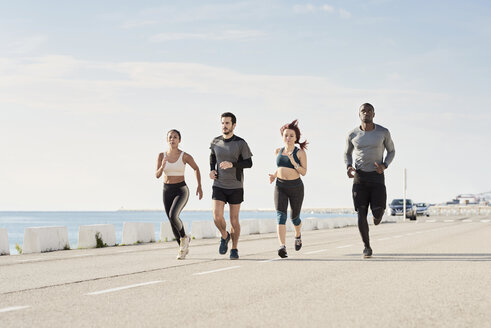 Group of sportspeople jogging at harbour - JNDF00026