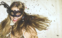 Young woman wearing a black eye mask at a party with confetti falling. - MINF06637