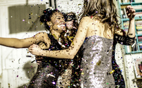 Four women wearing cocktail dresses dancing in a shower of confetti. - MINF06661
