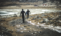 Two surfers wearing wetsuits and carrying surfboards walking along a snowy beach. - MINF06667