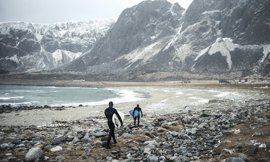 Two surfers wearing wetsuits and carrying surfboards walking along a beach with mountains behind. - MINF06670