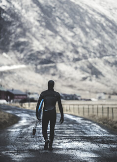Rear view of a surfer walking on a road wearing a wetsuit and carrying a surfboard. - MINF06673