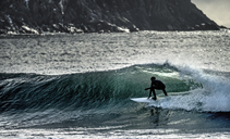 Young man surfing riding a wave to the shore, with cliffs behind. - MINF06676